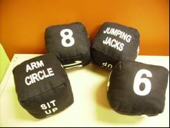 plush black dice with numbers and specific exercises on them