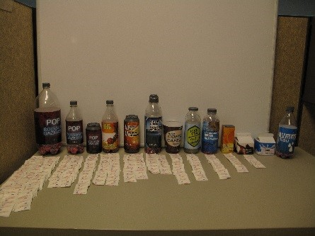 A display of beverage bottles with sugar packets in front of each bottle representing the amount of sugar in the respective bottles.