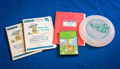 Photo of activity guide and frisbee (part of sun safety mini-kit)