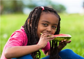 A young girl eating a slice of watermelon