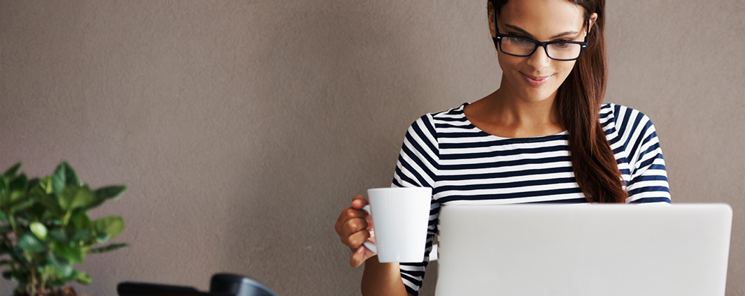 Woman holding a mug and looking at a laptop