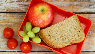 Photo of lunch container, including apple, cherry tomatoes, green grapes and half-sandwich on whole wheat bread