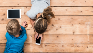 Photo of two children lying on the floor, playing on a phone and a tablet