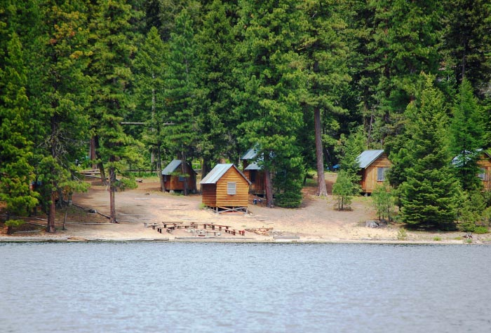 Log cabins in a forest close to the water