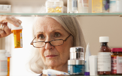 Woman looking at prescription bottles