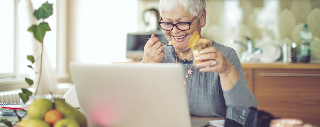 Older woman smiling at her computer and eating yogurt