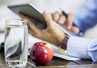 Glass of water and apple with a man holding a tablet in the background