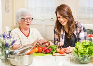 A dietitian helping out an older woman prepare vegetables
