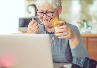 A woman eating while on her laptop