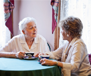 Two older woman having tea at a table