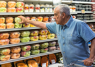 Man choosing honeydew melon at the grocery store