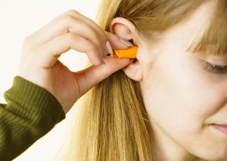 A woman putting in ear plugs