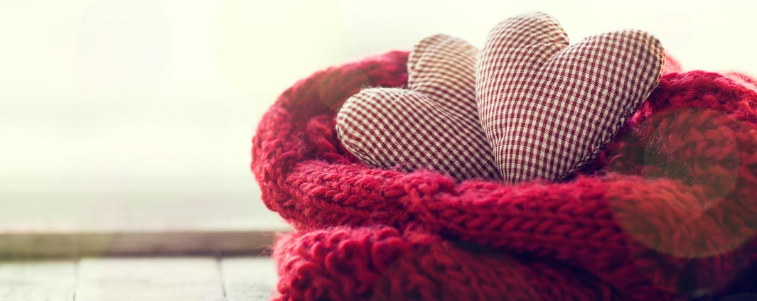 Two heart shaped pillows in a blanket