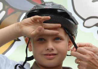 A child fitting his helmet securely