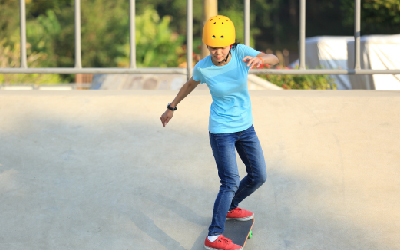 A girl wearing a helmet while on a skateboard