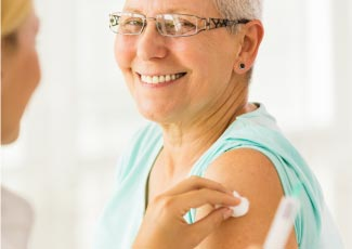 Nurse giving older adult vaccine