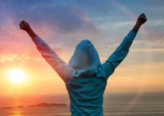 A woman wearing a hooded sweatshirt is looking out at the sunset with her arms up in the air