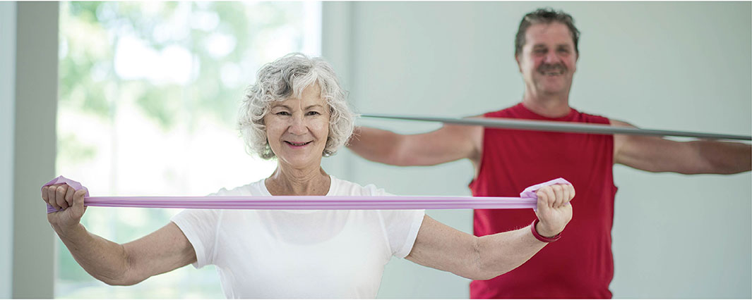 an older adult woman and an older adult man exercising their arms using a resistance band in a light colored room.