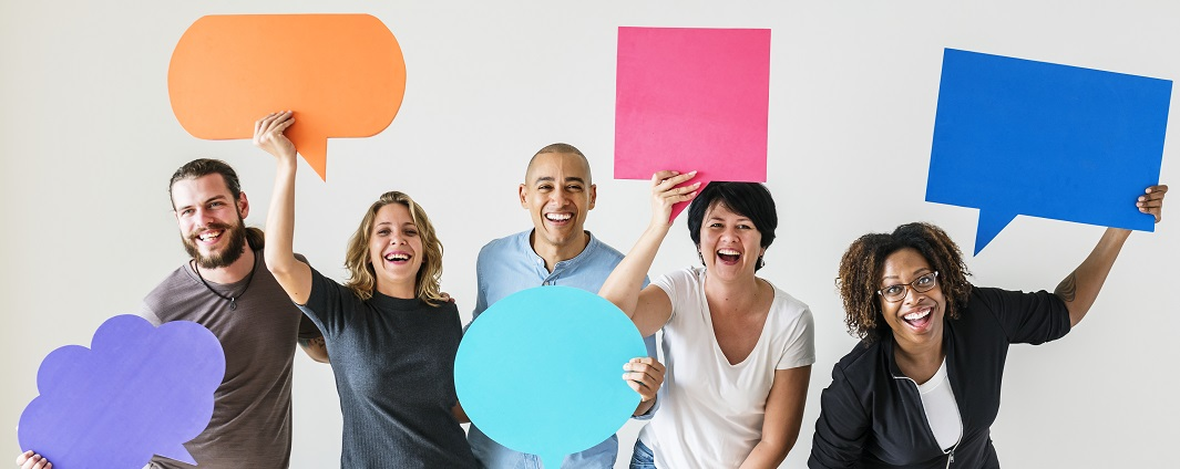 People holding large paper speech bubbles